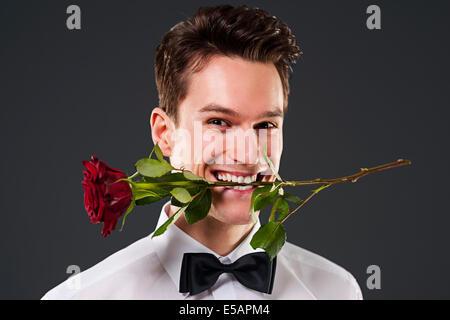 Homme avec une rose rouge dans la bouche, Debica, Pologne Banque D'Images