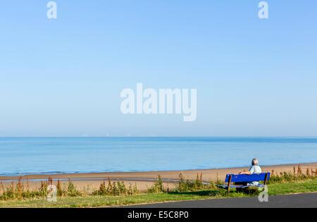 Homme assis sur un banc sur le front de mer de Thornton Cleveleys tôt le matin, au nord de Blackpool, Lancashire, Banque D'Images
