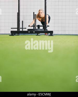 Jeune femme forte poussant le prowler sur gazon gazon artificiel. Mettre en place à l'aide des femmes à l'équipement Banque D'Images