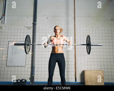 Jeune femme forte contre les pratiques de mettre en place dans une salle de sport. Mettre en place une femelle avec Banque D'Images