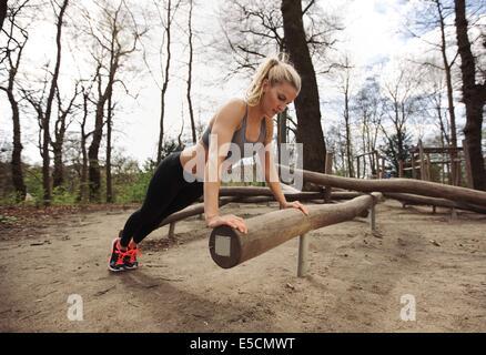 Jeune femme fit l'exercice dans le parc. Fort et musclé jeune femme faisant pompes sur un journal. Banque D'Images