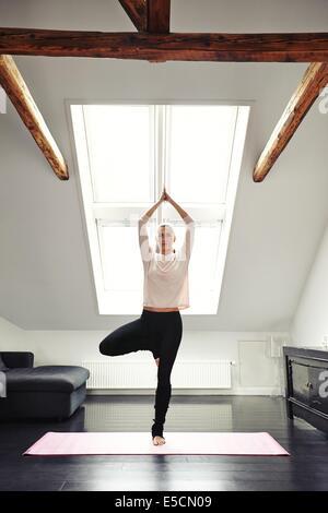 Jeune femme pratiquant le yoga dans la salle de séjour. Femelle en bonne santé debout sur une jambe et la méditation à la maison. Mettre en place des femmes en posture de l'arbre d