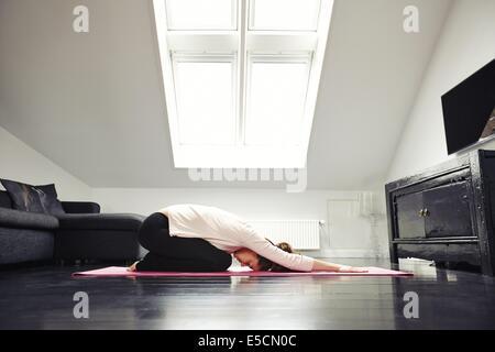 Vue latérale du young caucasian woman exercising yoga dans son salon. Femme faisant exercice de relaxation sur le tapis à la maison. Banque D'Images