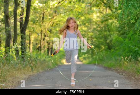 Petite fille saute par-dessus la corde dans l'forest Banque D'Images