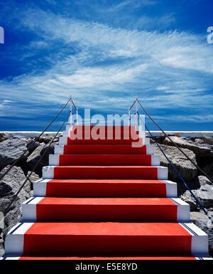 Tapis rouge escalier menant au ciel avec des barrières des deux côtés des poteaux Banque D'Images
