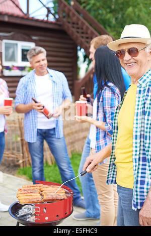 Portrait of happy senior man saucisses à frire et regardant dans la campagne à week-end avec groupe de jeunes amis Banque D'Images