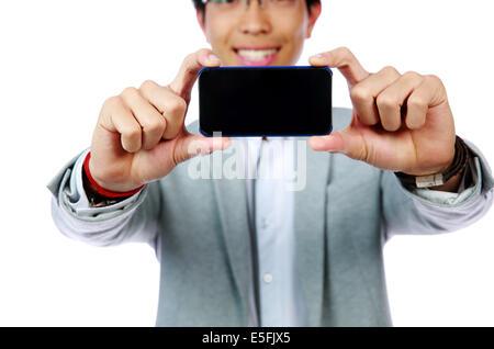 Happy asian man making photo sur smartphone. L'accent sur le smartphone. Banque D'Images