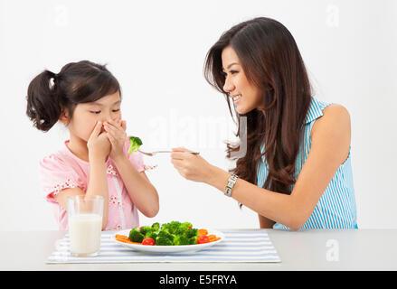Asian mother essayer de nourrir sa fille qui n'aime pas les légumes Banque D'Images