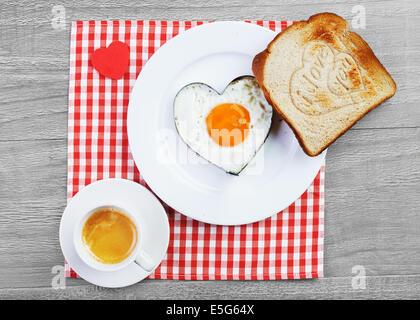 Des oeufs au plat en forme de coeur et des toasts avec amour message.Le petit-déjeuner pour un être cher Banque D'Images