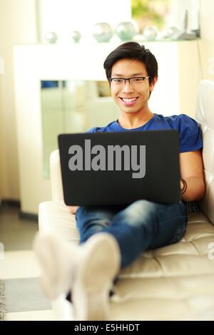 Les jeunes asiatiques heureux homme étendu sur le canapé avec un ordinateur portable à la maison Banque D'Images
