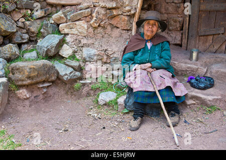 Les Indiens Quechua mature femme portant un chapeau assis sur une pierre en face d'une embrasure, Cordillera Huayhuash, Banque D'Images