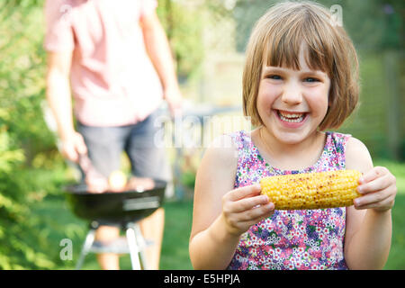 Young Girl Eating Maïs doux au barbecue familial Banque D'Images