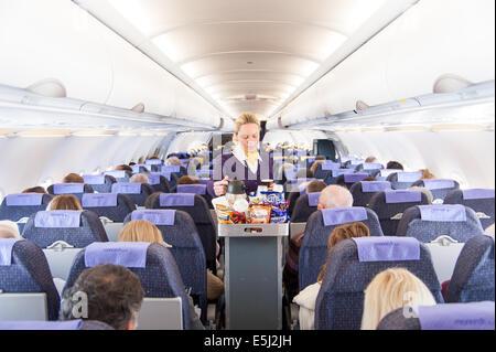 L'hôtesse de l'air de Monarch Airlines sert des collations à partir du chariot de boissons, Royaume-Uni