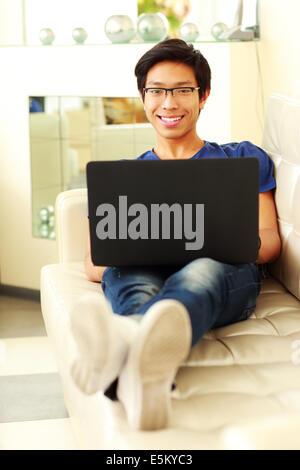 Cheerful asian man allongé sur le canapé avec un ordinateur portable à la maison Banque D'Images