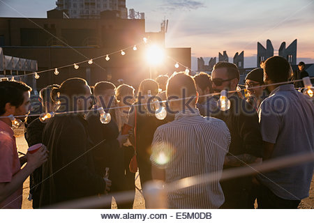 String lights sur crowd at rooftop party Banque D'Images