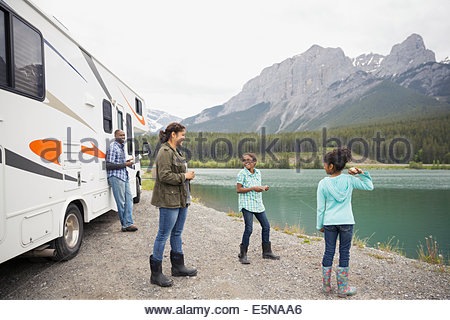 Family standing at lakeside près de RV Banque D'Images