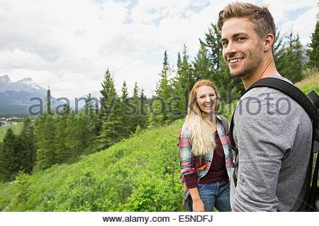 Smiling couple randonnées près des montagnes Banque D'Images