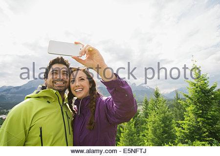 Couple talking près des montagnes selfies Banque D'Images