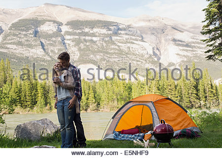 Couple hugging hors camping lakeside Banque D'Images