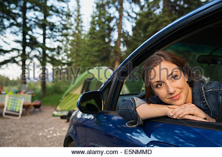 Smiling woman in car au camping Banque D'Images