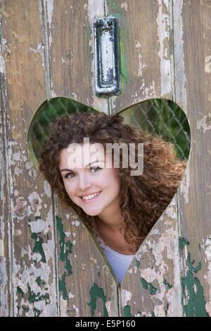 Adolescent à la recherche par forme de coeur découpe dans une vieille porte Banque D'Images