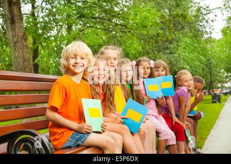 Les enfants avec les portables bleu s'asseoir dans la rangée sur l'établi Banque D'Images