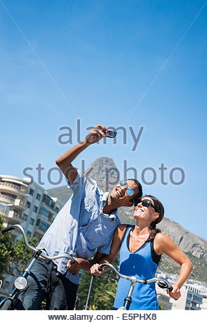 L'homme et la femme couple taking a photo Selfies en face de Lion's Head mountain à Camp's Bay Beach, Cape Town, Banque D'Images