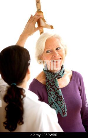 La mesure de la hauteur du médecin une patiente lors de la consultation médicale. Banque D'Images
