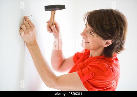 Do-it-yourself, martelage femme clou dans mur. Banque D'Images