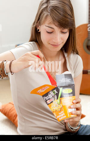 Teenage girl eating Pasta Box®. Banque D'Images