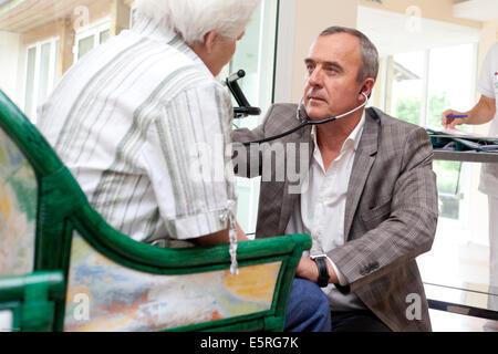 Médecin généraliste parlant avec une personne âgée au cours d'une visite dans une maison de retraite, Dordogne, Banque D'Images