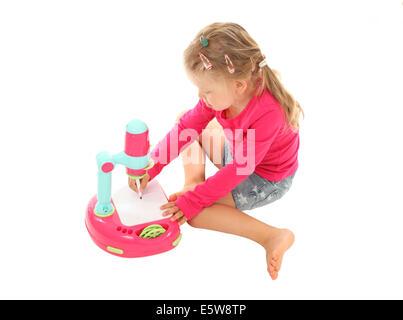 Petite fille dessin photo avec un jouet projecteur Banque D'Images
