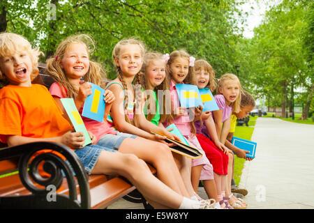 Heureux les enfants assis sur un banc dans une rangée Banque D'Images