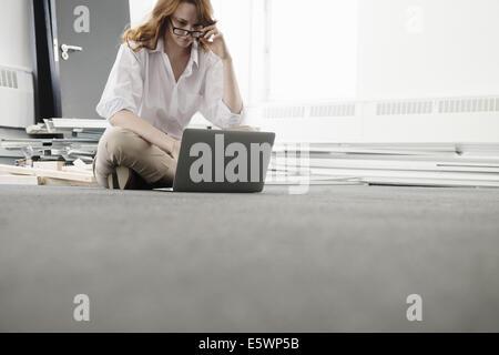 Mid adult woman using laptop in nouveau bureau Banque D'Images