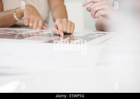 Cropped shot de deux mains de femmes d'affaires et du plan directeur