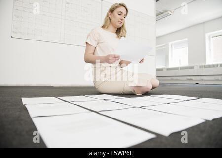 Young businesswoman organiser la paperasse sur office marbre Banque D'Images