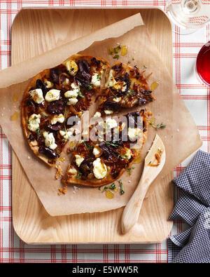 Pizza aux oignons caramélisés sur planche à découper Banque D'Images
