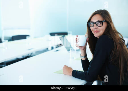 Portrait of businesswoman drinking coffee at conference table Banque D'Images