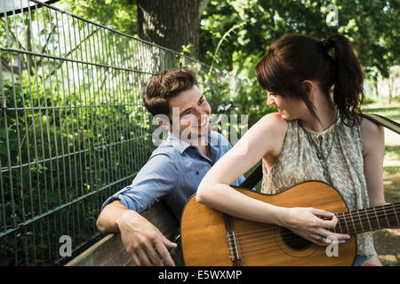 Jeune couple playing acoustic guitar in park Banque D'Images
