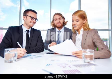 Groupe de partenaires d'affaires de discuter des articles à meeting in office Banque D'Images