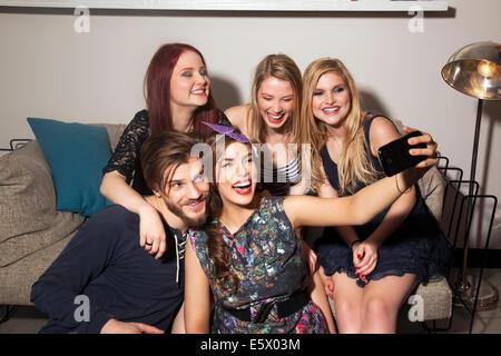 Les amis de prendre le canapé selfies Banque D'Images