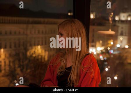 Young woman enjoying view à partir de la chambre d'hôtel, Vienne, Autriche Banque D'Images