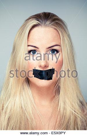 Close up portrait of mid adult woman avec du ruban adhésif sur sa bouche Banque D'Images