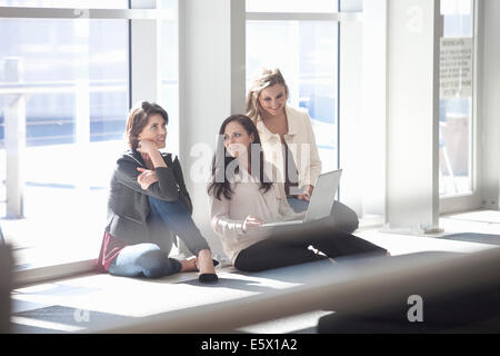 Trois businesswomen sitting on floor with laptop in conference centre Banque D'Images