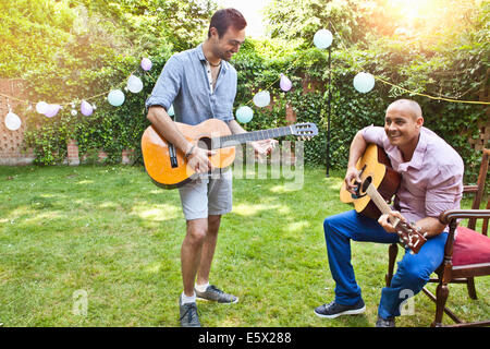 Deux amis playing acoustic guitar in garden Banque D'Images