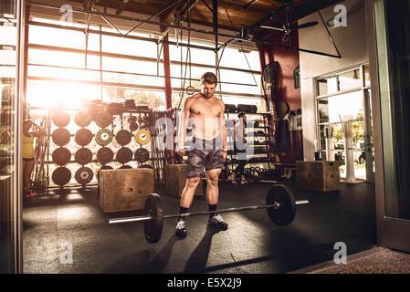 Regardant le bodybuilder barbell in gym Banque D'Images