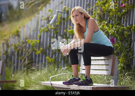Femme assise sur le dessus de banc de parc Banque D'Images