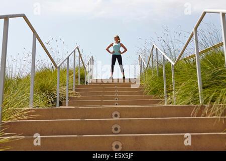 Femme debout du haut des escaliers Banque D'Images