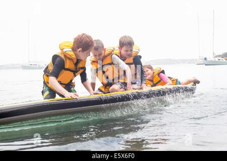Frères et soeur à propos de tomber de paddleboard dans la mer Banque D'Images