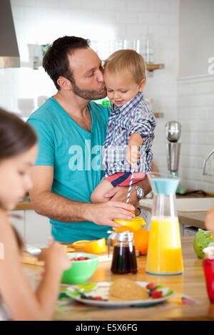 Mid adult man multi tasking petit-déjeuner avec son fils et sa fille Banque D'Images